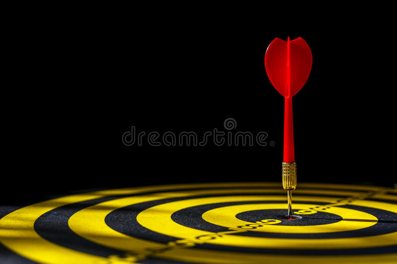 Red dart arrow in the center of dartboard. Isolated on black background stock image