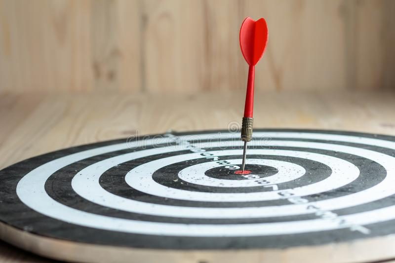 Red dart arrow hit the center target of dartboard metaphor marketing competition concept. On wood background royalty free stock image