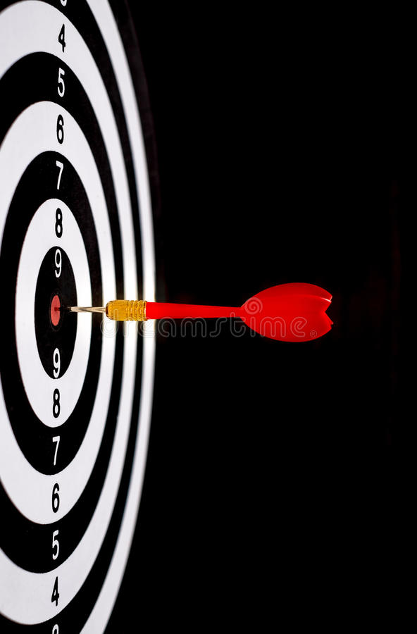 Red dart arrow hitting in the target center of dartboard. With black background royalty free stock photography