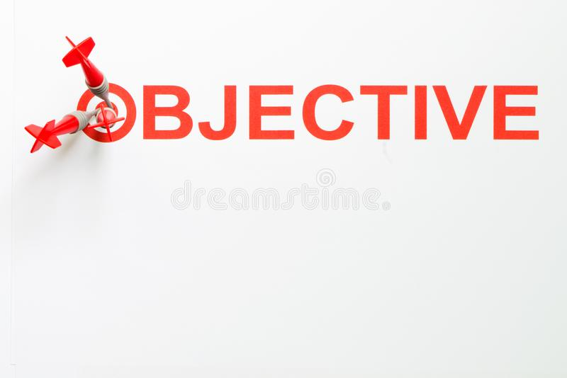 Objective text with dart on target. Red dart hit on target with objective text isolated on white background stock photos
