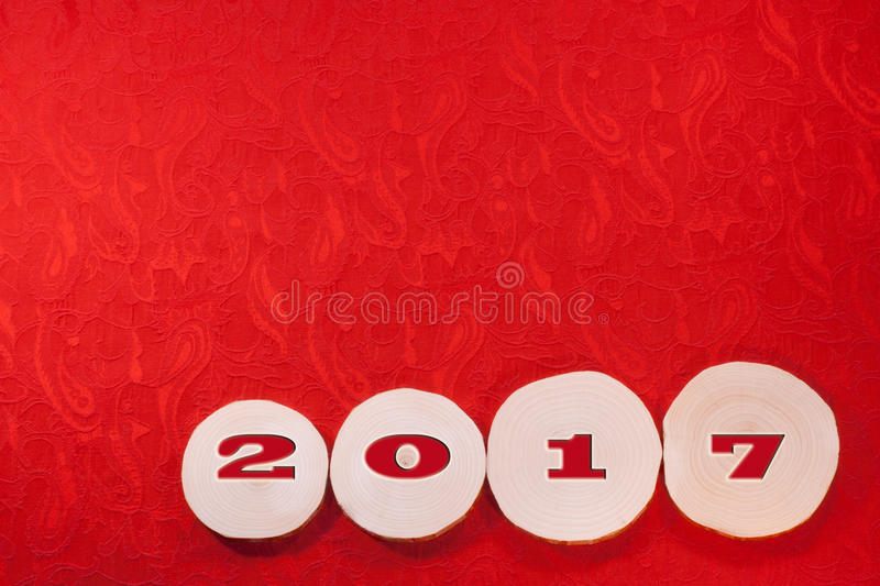 Red date 2017 on alder saw cuts on red ornate ethnical fabric ba. Ckground. Christmas and New Year's background royalty free stock photo