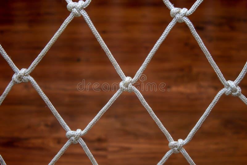 Red de la cuerda de una hamaca, contra una lamina de madera imágenes de archivo libres de regalías