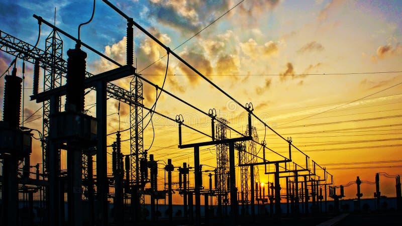 Red de la electricidad en la estación del transformador en salida del sol imagenes de archivo