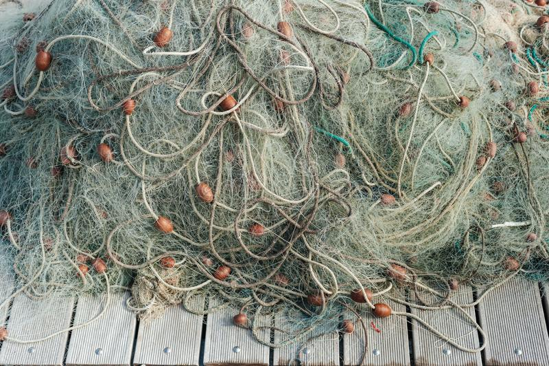 Red de pesca de nylon con las boyas en fondo de madera fotos de archivo