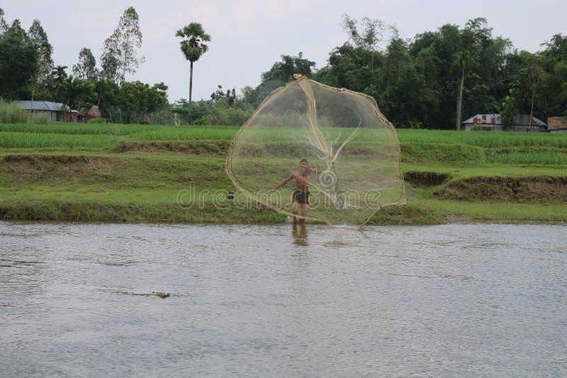 Red de vuelo - pescado de Catching del pescador del pueblo en el río imagen de archivo