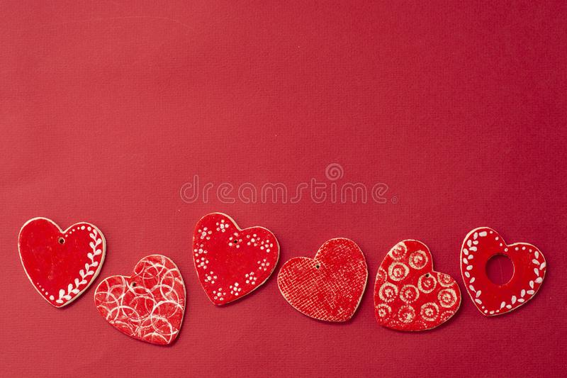 Red decorative hearts over red background. Valentine's Day, love celebration. Copy space. Top view royalty free stock images