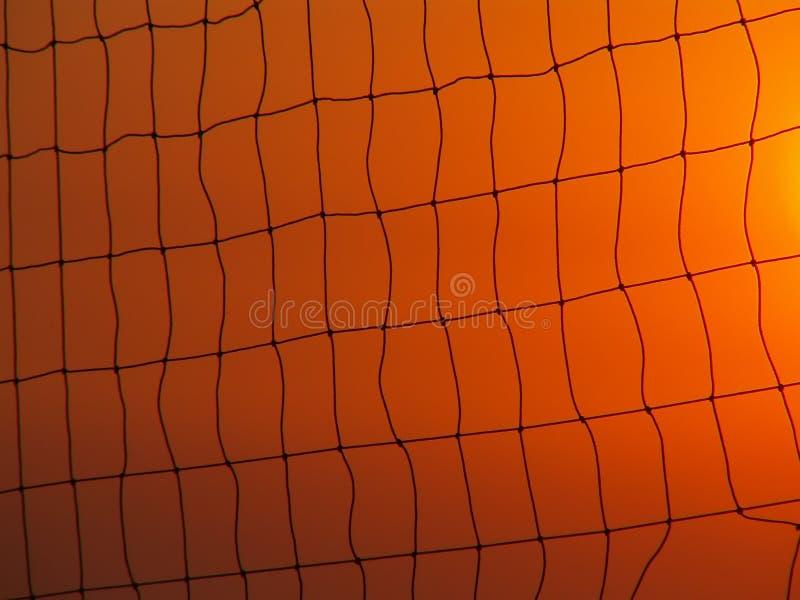 Red del voleibol en el cielo de la puesta del sol foto de archivo