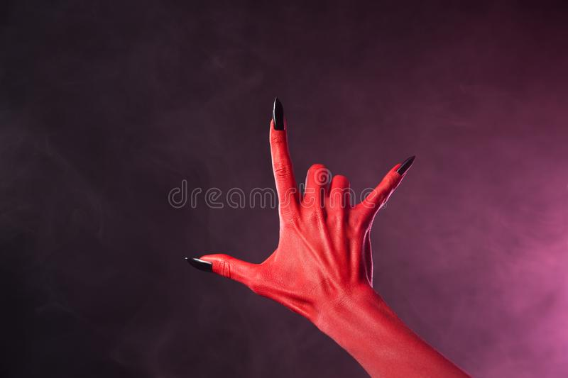Red devil hand with black nails showing heavy metal symbol. Halloween theme royalty free stock images