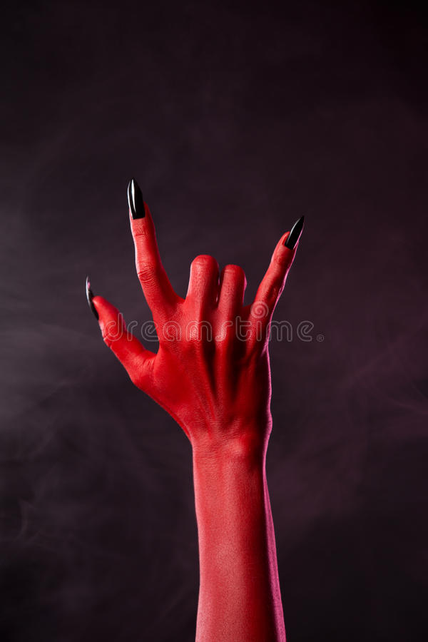 Red devil hand showing heavy metal gesture. Studio shot on smoky background stock photos
