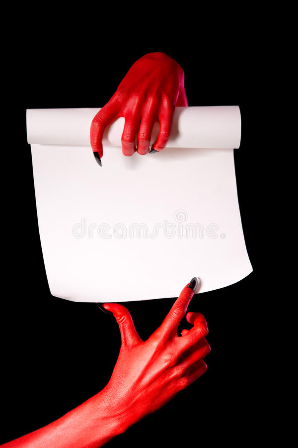 Red devil hands with paper scroll stock photography