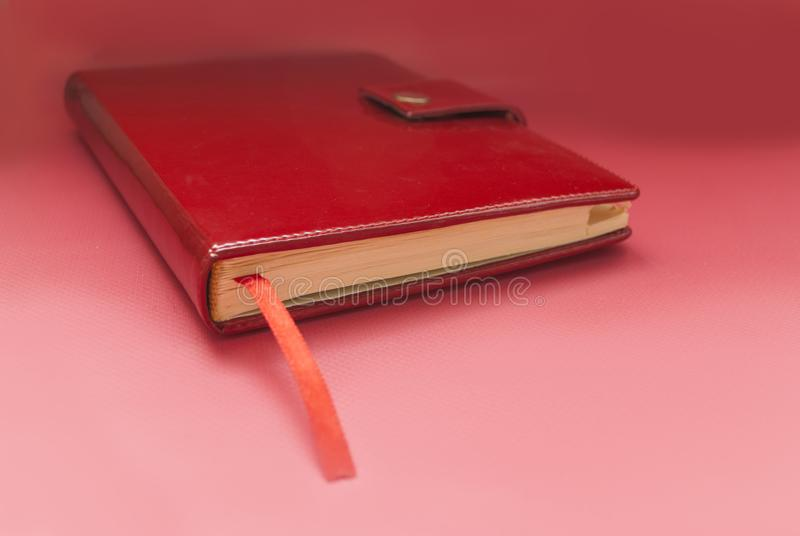 Red diary bookmark on a pink background stock image