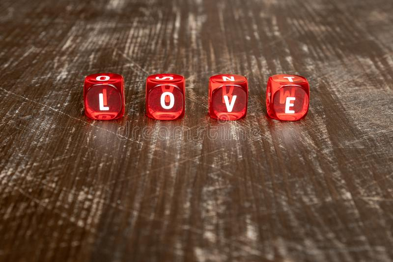 Red dice with word LOVE. Red dice over wooden background with word written LOVE stock image