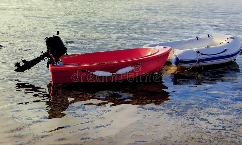Sailing Dinghies Moored . Isolated. Red dinghy with outboard engine moored together with with small white tender. Stock Image royalty free stock image