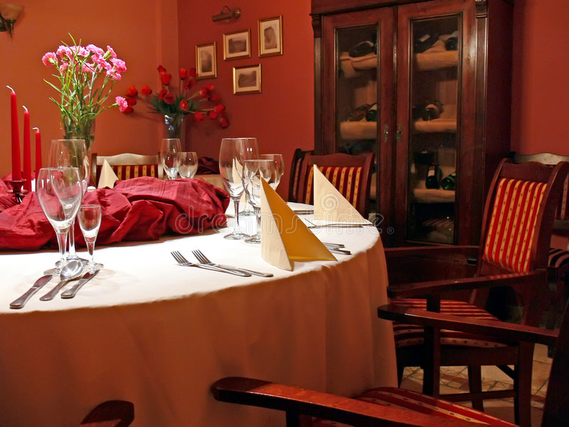 Red dining room details. Posh dining room with red walls. A round table with stylish chairs. Candlestick, flowers, glasses and cutlery royalty free stock image