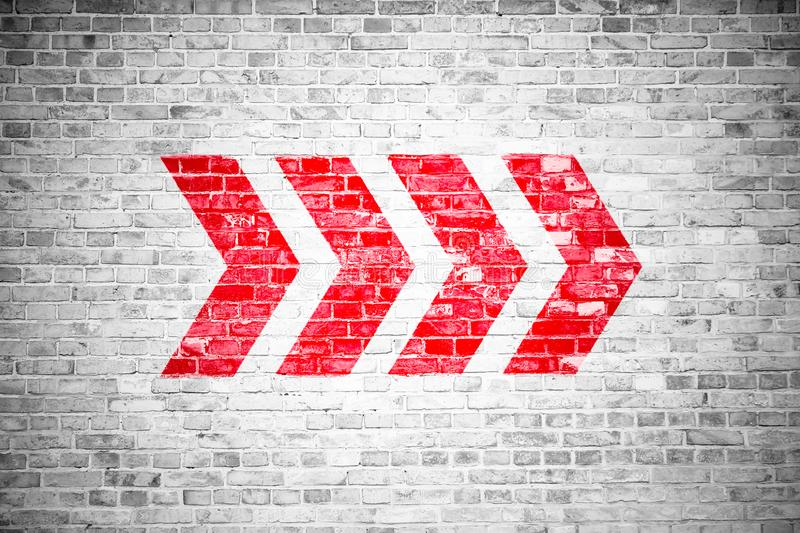 Red directional arrow signs pointing direction painted on a white gray brick wall signboard texture background stock image