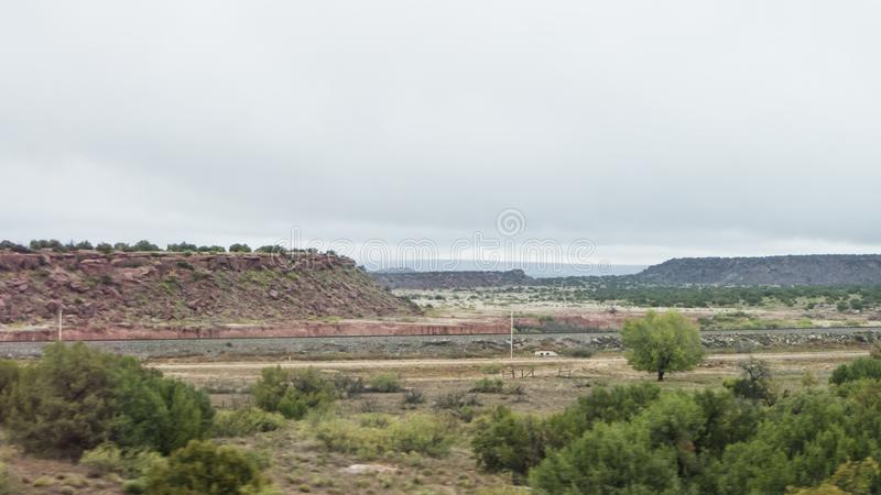 Eastern New Mexico landscape railroad tracks and mountains. Red dirt, desert shrubs, distant mountains and gloomy clouds are features of this Eastern New Mexico royalty free stock photography
