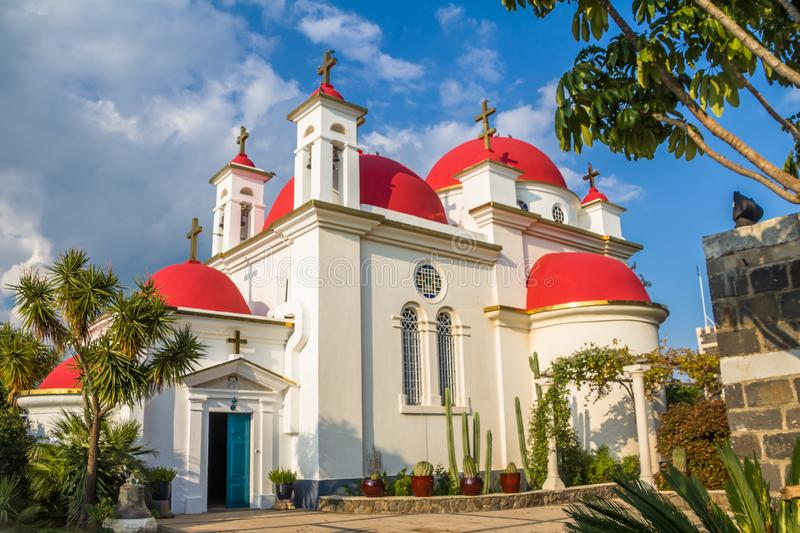 The red-domed Greek Orthodox church of the Twelve Apostles near the shore of the Sea of Galilee at Capernaum, Israel. The church aka the Church of the Seven stock photography