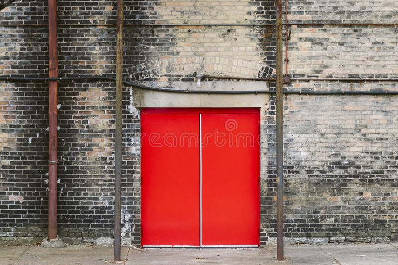 Red door on brick building royalty free stock photography