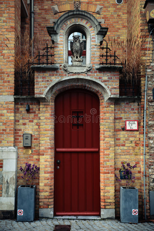 Red door on the brick wall of the house in Bruges, Belgium. 2016 royalty free stock photos