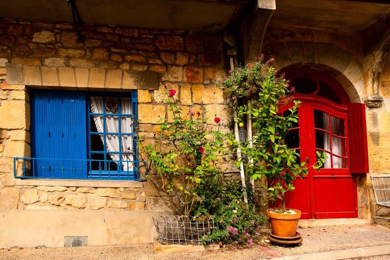 Red door Green roses Saint-Cyprien Dordogne stock image