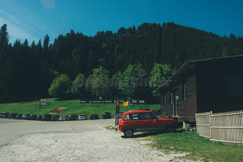 Red 5-door Hatchback Near the Brown Wooden House in Daytime stock images