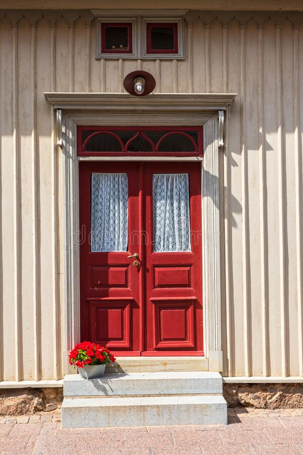 Red door on an old house with a flower pot stock photography