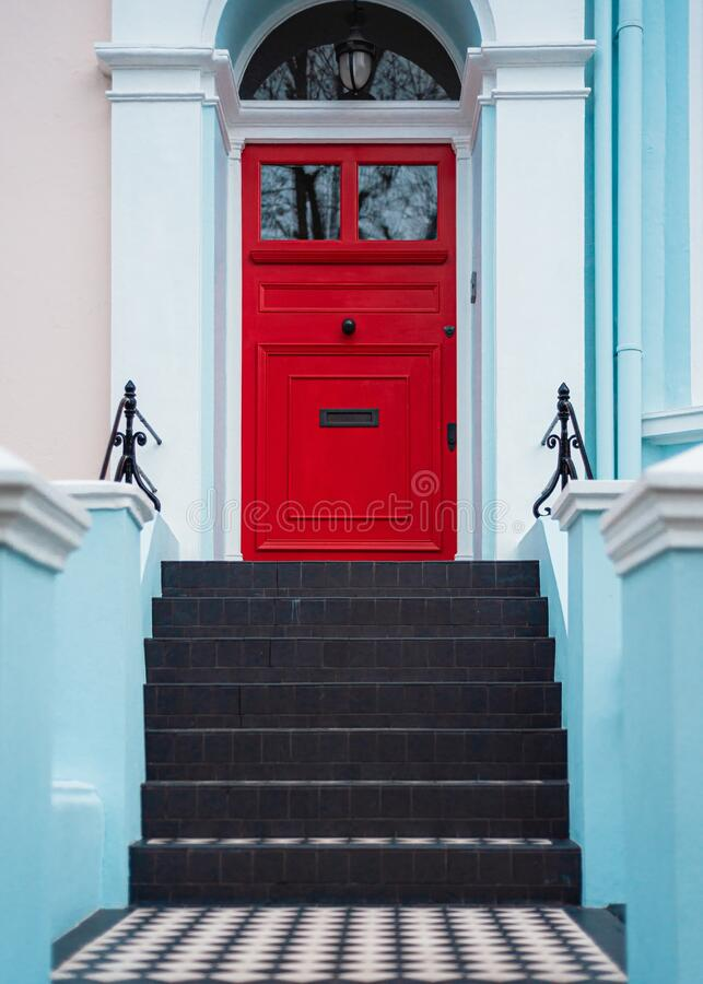 Red door with stairs and blue walls. Red entrance door with stairs and blue walls royalty free stock photos
