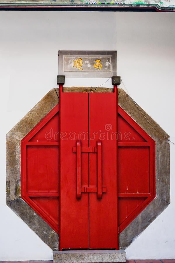Octagonal red door, entrance to buddhist Taiwanese temple, Tainan, Taiwan royalty free stock image