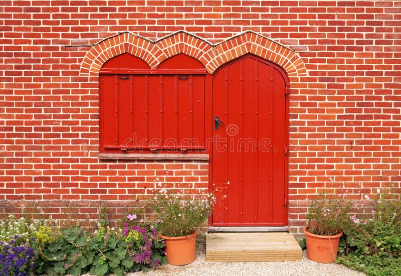 Red door and windows on red brick wall stock photography
