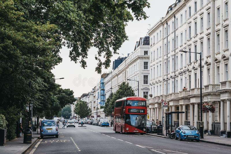 Red double decker bus driving past a row of white terraced houses on a street in Pimlico, London, UK. London, UK - July 16, 2019: Red double decker bus driving stock photography