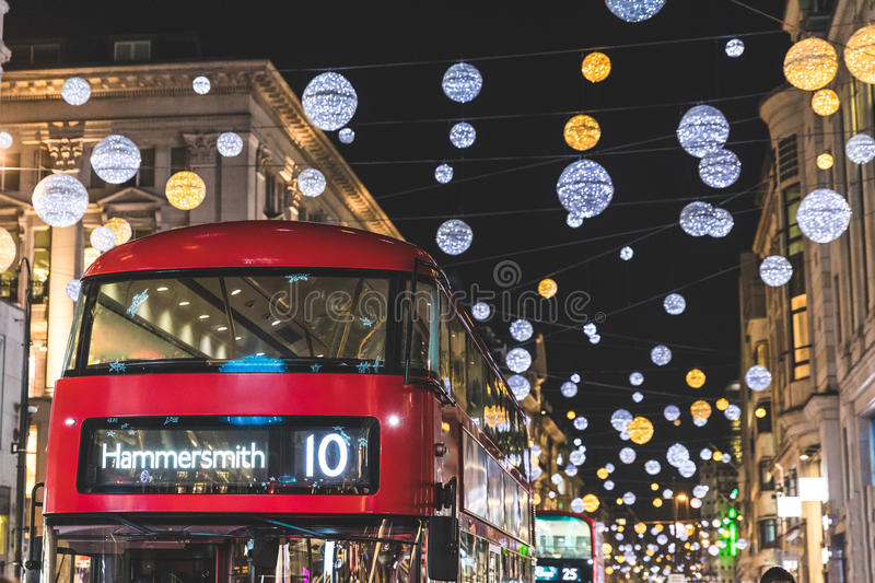 Red double decker bus in London during Christmas time. Lights and decorations over the famous London street reflecting on the bus surface. Travel and tourism royalty free stock photos