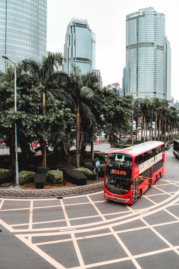 Red double-decker bus passing around palm trees stock photos