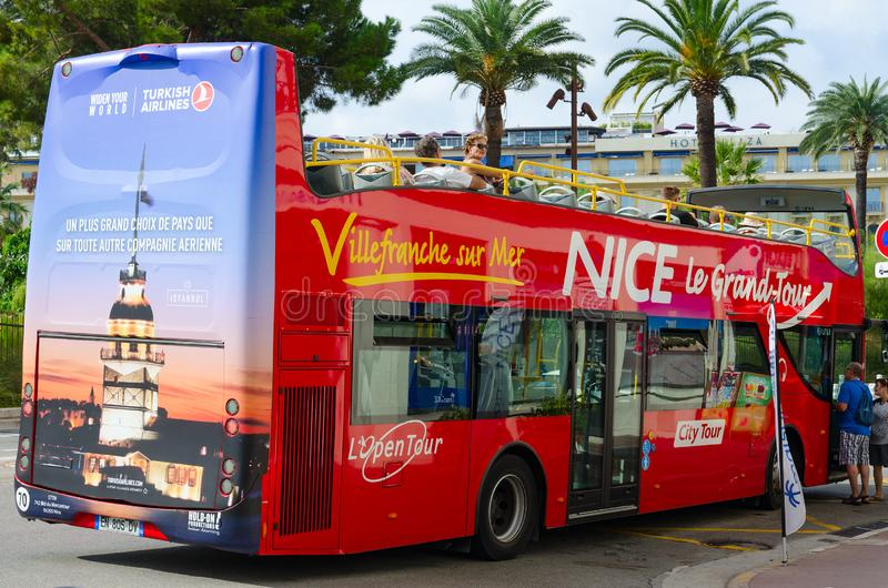 Red double decker sightseeing bus Nice Le Grand Tour in city center, Nice, France. NICE, FRANCE - SEPTEMBER 15, 2018: Unidentified tourists sit in red double stock image