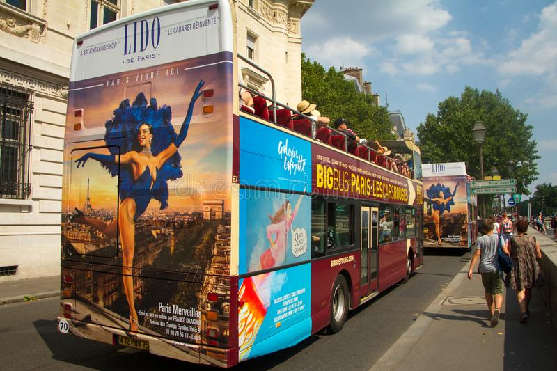 Red Double Decker Tourist bus on the street of Paris near Pont Nef with images of popular architectural landmarks royalty free stock photography