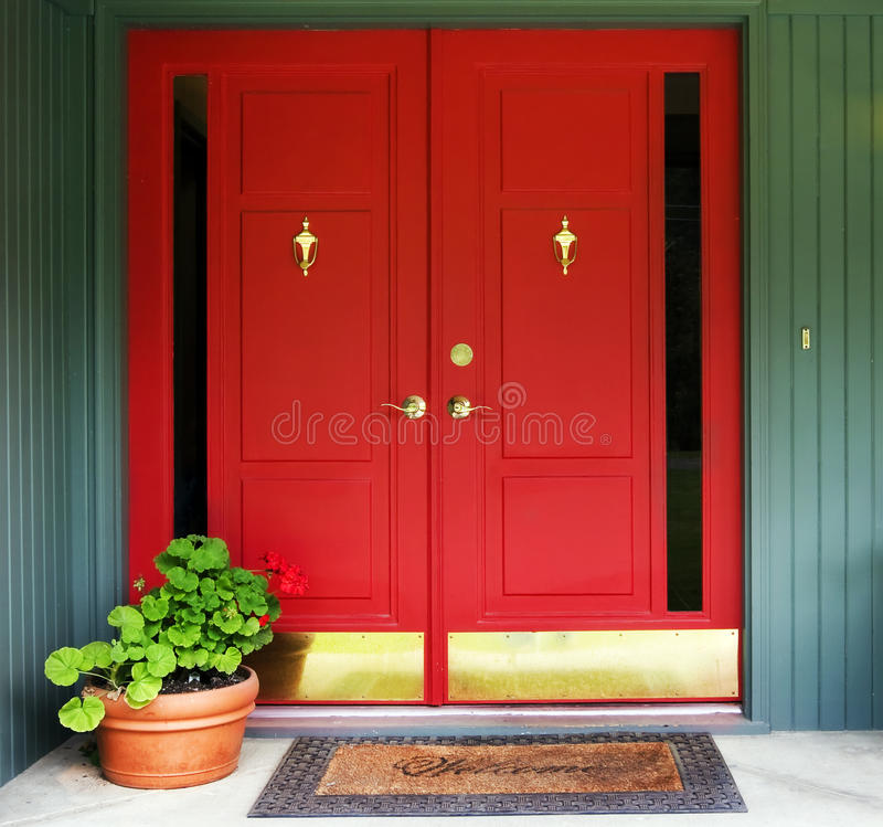 Red Double Door Entry. With brass fittings, welcome mat and terracotta pot of geraniums with red blossoms royalty free stock images