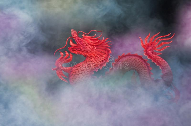 Red dragon in beautiful colored smoke. Of fire in the dark stock images