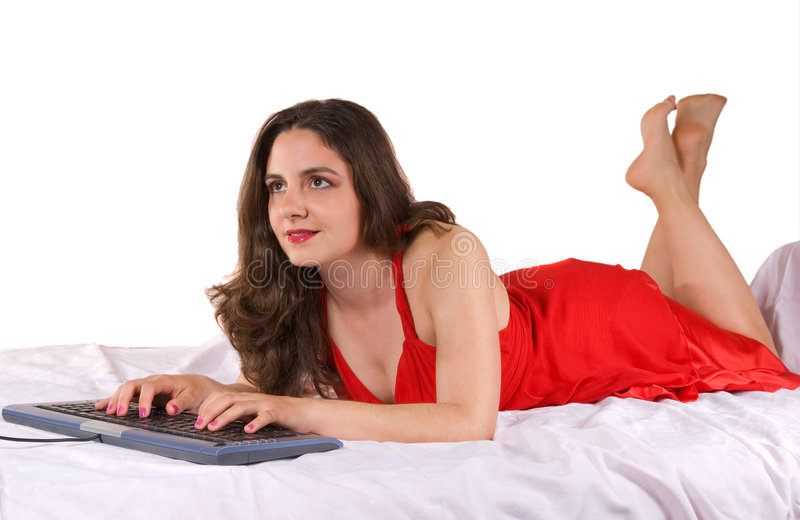 Red dress beautiful girl typing on keyboard in bed. A beautiful girl, lying on a couch in attractive red dress, typing on a keyboard stock photo