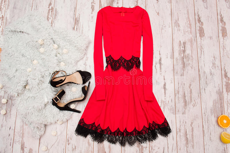 Red dress with lace, black shoes and a Imitation fur on a wooden background, fashionable concept, top view.  royalty free stock photography