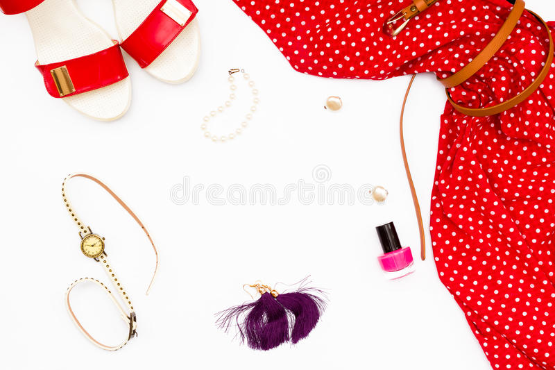Red dress, shoes, watches, nail Polish and earrings on a white background. feminine concept beauty. royalty free stock image