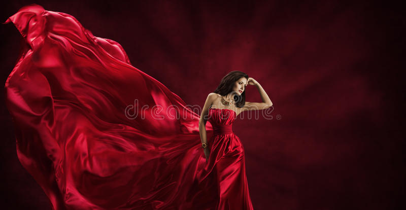 Red Dress, Woman in Flying Fashion Silk Fabric Clothes Model. Red Dress, Woman in Flying Fashion Silk Fabric Clothes, Model Posing with Blowing Waving Cloth royalty free stock photo