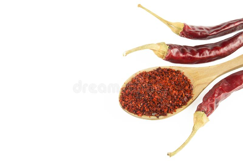 Red dried crushed hot chili pepper flakes or powder in wooden spoon isolated on white background royalty free stock image