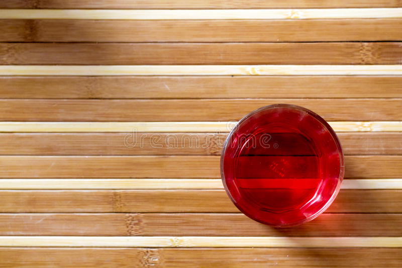 Red drink on bamboo floor stock images