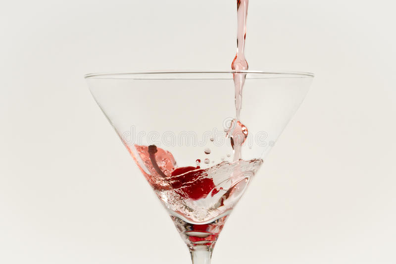 Red drink pouring down into grass with cherry stock image