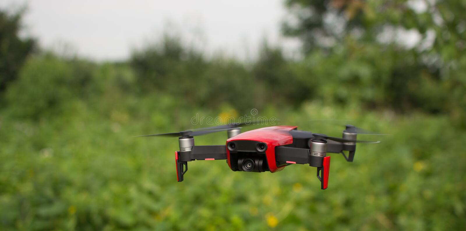 Red drone hovering in the air. Small sized red drone is hovering in the air with green plants in the backgrtound royalty free stock images