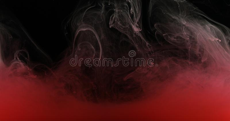 Red Ink Paint in Water Creating Liquid Artistic Shapes. Red drops, waves and clouds of ink creating dynamic shapes in water. Abstract effects of paint colors in royalty free stock image