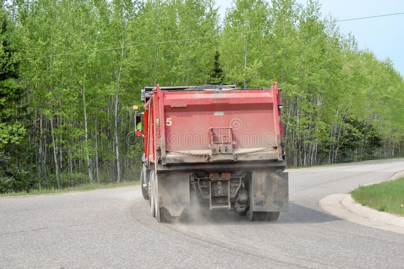 Red Dump Truck Driving Down Curvy Road stock photography