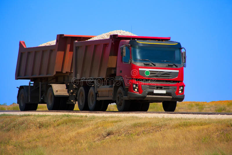 Red dump truck with the trailer. Loaded with rubble royalty free stock photography