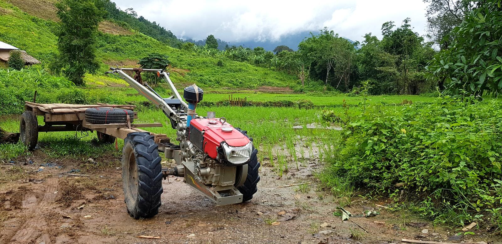 Red E-taen Thai tractor modifies to used for the shuttle and pick up or drop off people parked on mud ground royalty free stock photo