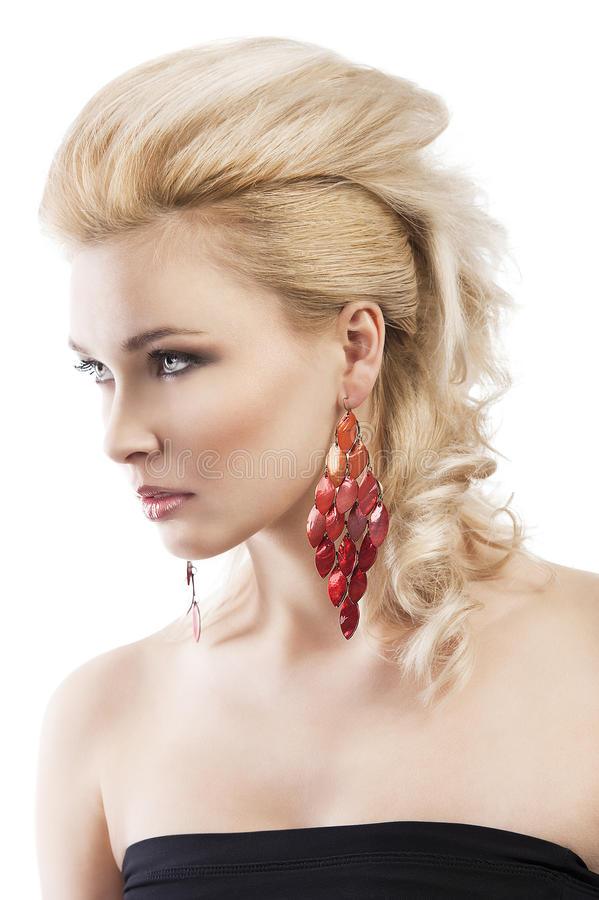 Red earring on cute blond girl, she is turned royalty free stock image