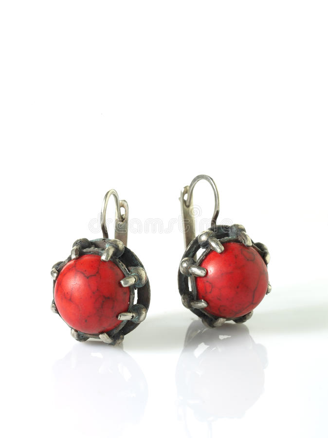 Red earring. Red silver earring over white with shadows royalty free stock images
